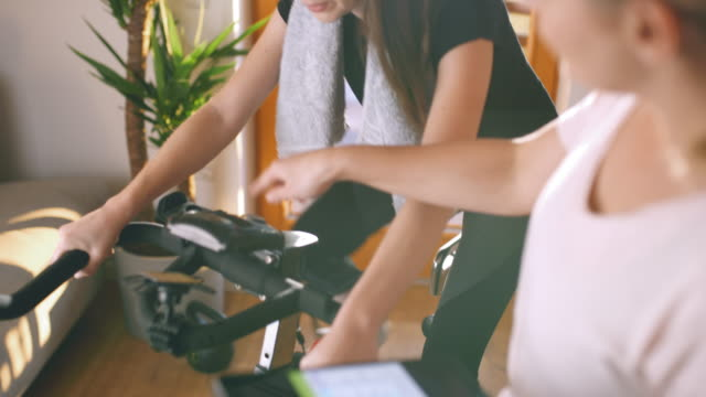 slo mo female coach with a digital tablet assisting a woman cycling on the exercise bike - exercise bike stock videos & royalty-free footage