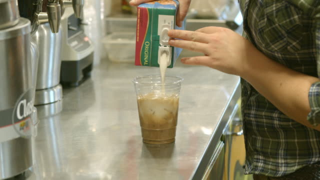 female coffee house barista pours milk into iced chai latte cup and  blends liquids by twirling the serving cup / redlands, california, usa - pouring milk stock videos & royalty-free footage