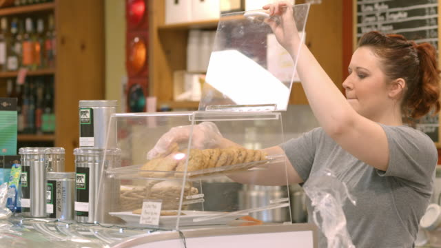 female coffee house barista wearing protective glove places chocolate chip cookies into pastry display case / Redlands, California, USA