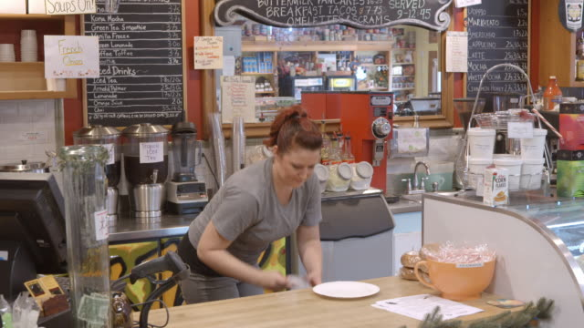 female coffee house employee puts on single use glove to retrieve pastry from display case and serve it on paper plate and then removes glove and throws glove into trash / redlands, california, usa - paper plate stock videos & royalty-free footage