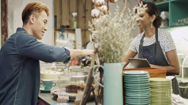 Weibliche Coffee-Shop-Besitzer mit Kaffee an Kunden