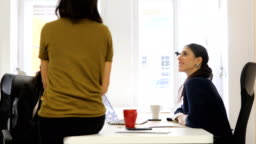 Female colleagues discussing at desk in start up