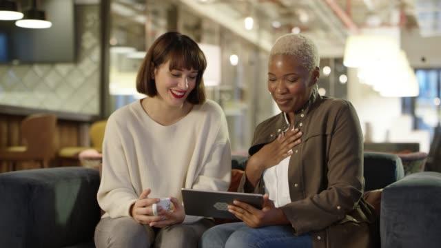 kollegen teilen digitales tablet im büro - designer einrichtung stock-videos und b-roll-filmmaterial