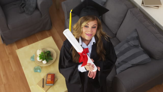 stockvideo's en b-roll-footage met female college graduate holding diploma and smiling - afstudeer toga