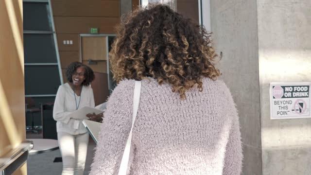 vídeos de stock, filmes e b-roll de universitária entra na sala de aula - universidade comunitária