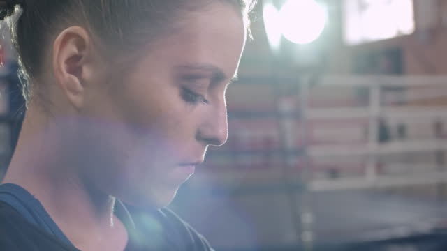 Female combat athlete putting on protective boxing hand wraps