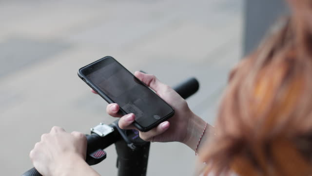 stockvideo's en b-roll-footage met female commuter scanning qr code on electric bicycle - autoreis
