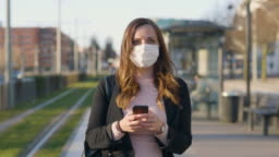 Female commuter with a protective medical face mask in the city