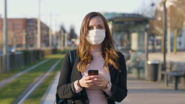 female commuter with a protective medical face mask in the city - surgical mask stock videos & royalty-free footage