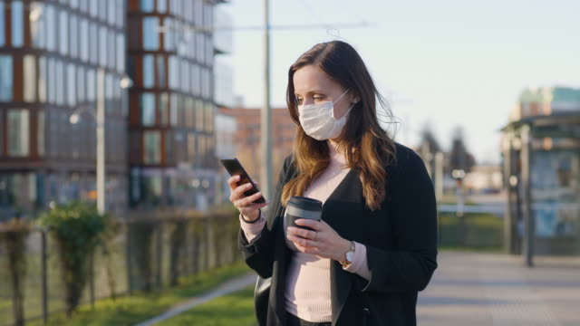 vídeos de stock e filmes b-roll de female commuter with a protective medical face mask in the city - a caminho