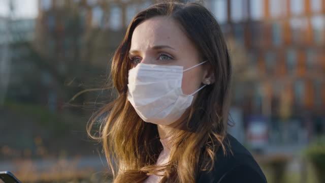 stockvideo's en b-roll-footage met vrouwelijke forens met een beschermend medisch gezichtsmasker in de stad - operatiemasker