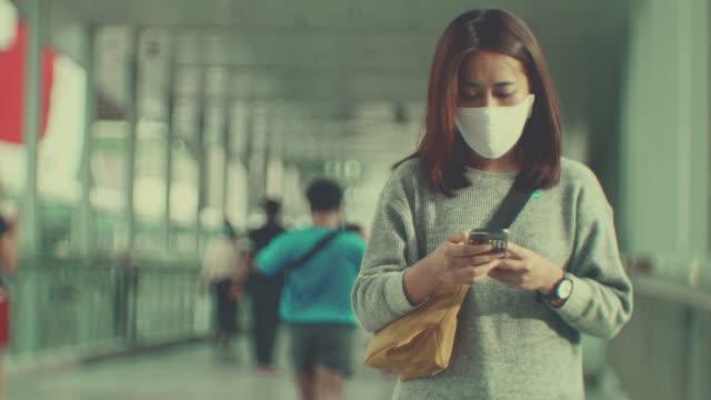 市内の保護医療フェイスマスクを持つ女性通勤者 - image点の映像素材/bロール