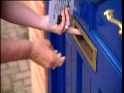 female conservative party worker drops leaflet through letterbox canvassing for leicester by election 09 jul 04 - レターボックス点の映像素材/bロール