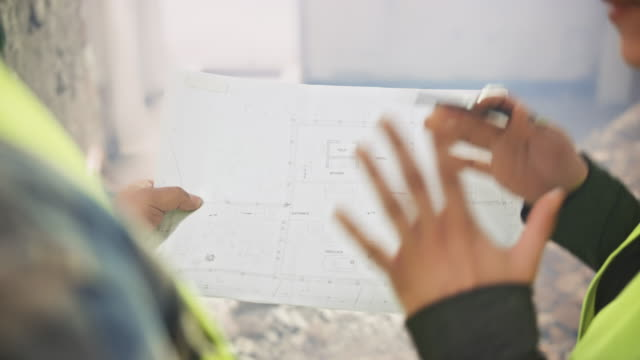female construction manager explaining details of the plan the foreman is holding in his hands - caposquadra video stock e b–roll