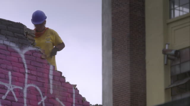 Female construction worker breaks away portions of graffiti painted brick wall with sledgehammer.