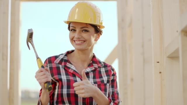 vídeos de stock, filmes e b-roll de trabalhador da construção civil feminino segurando o martelo e mostrando polegares para cima - capacete equipamento