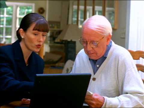 Female consultant with laptop handing papers to + shaking hands with senior man sitting at table