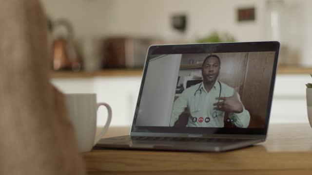 vidéos et rushes de female consulting doctor from home during video call on laptop in kitchen during pandemic - vue de par dessus l'épaule