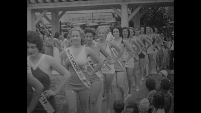 female contestants parade in line approaching camera wearing bathing suits with sashes bearing the names of their sponsors during local outdoor... - beauty pageant stock videos and b-roll footage