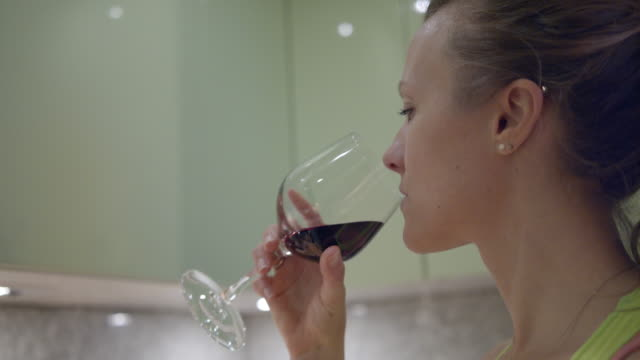 female cook drinks wine while preparing food - rubbing alcohol stock videos & royalty-free footage