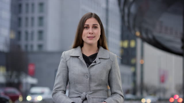 Female correspondent reporting from the city center