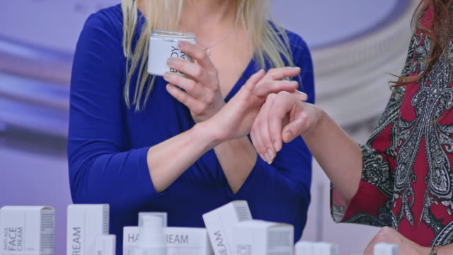 female cosmetic line presenter placing some cream on the female model's hand in the tv show - television advertisement stock videos & royalty-free footage
