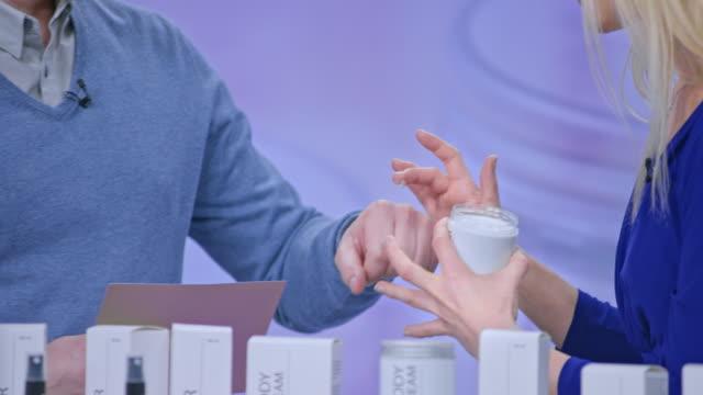 Présentateur de ligne cosmétique féminine peu de crème sur le dos de la main de l'homme animateur de l'émission à friction