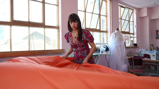 female costumier in early 40s unrolling large bolt of cloth - workbench stock videos & royalty-free footage