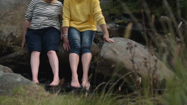 female couple dipping their feet in river - walking in water stock videos & royalty-free footage