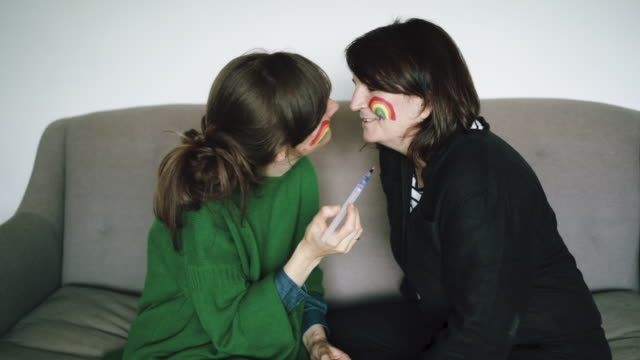 female couple face painting ready for pride - annual event stock videos & royalty-free footage