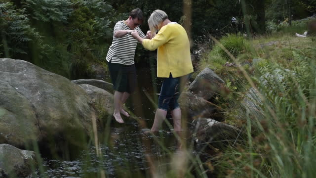 female couple playing in stream - walking in water stock videos & royalty-free footage