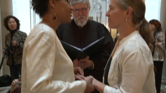 vídeos de stock e filmes b-roll de ms female couple reciting wedding vows at san francisco city hall/ zi cu woman putting ring on partner's finger/ san francisco california/ audio - votos matrimoniais