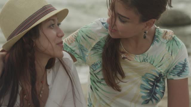 stockvideo's en b-roll-footage met a female couple sitting by a small bonfire. - hemden en shirts