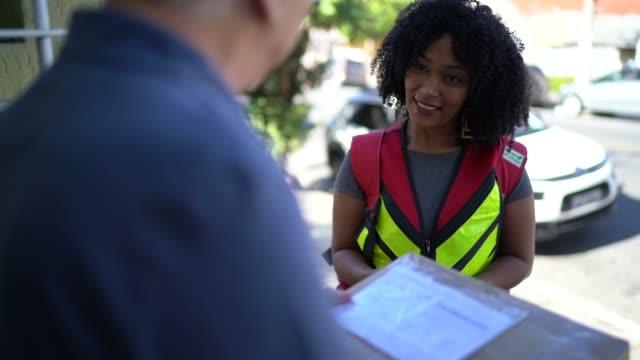 vídeos de stock, filmes e b-roll de entregador feminino entregando pacotes para o idoso em sua porta da frente - carteiro