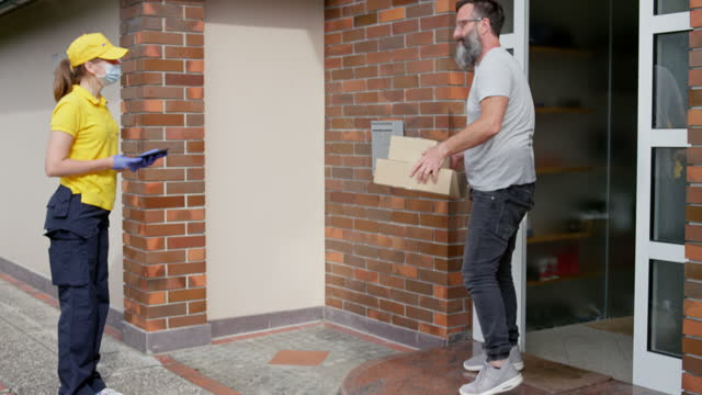vídeos de stock e filmes b-roll de female courier wearing protective mask and gloves bringing a parcel to the front door and stepping to the side after client picks up the delivery - amarelo