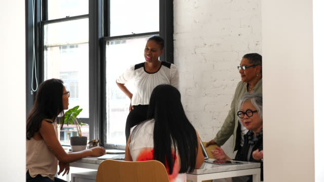 ms female coworkers in discussion during team meeting in creative office - brainstorming stock videos & royalty-free footage