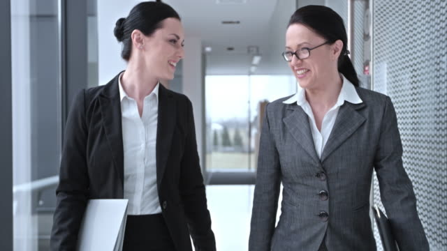 slo mo ds female coworkers talking while walking down hallway - businesswoman stock videos & royalty-free footage