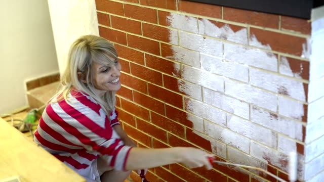 Female craftsman painting wall with paint roller.