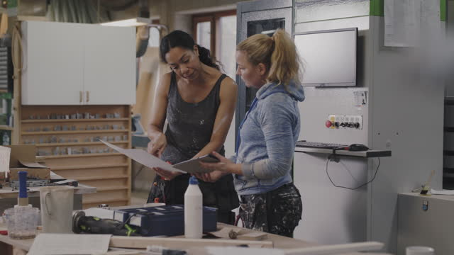 female craftsperson consulting coworker while discussing over document and digital tablet at workshop - casual clothing stock videos & royalty-free footage