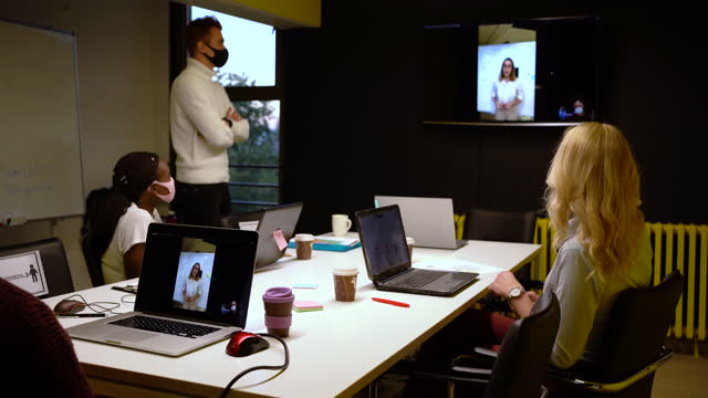 female creative director explaining the project to her team during web conference in a board room while all in team wearing protective face mask for their safety - business meeting stock videos & royalty-free footage