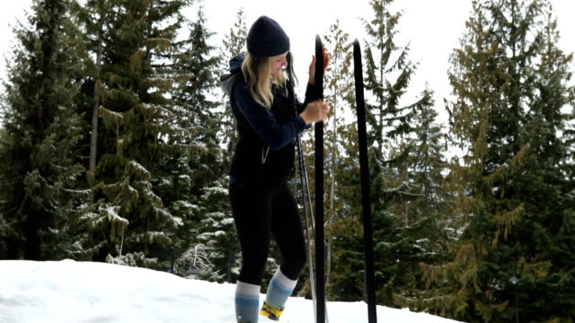 female cross country skier prepares for a ski through snowy forest - independence stock videos & royalty-free footage