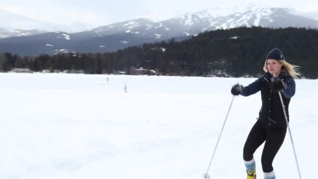 female cross country skier traverses lakeshore course - sci e snowboard video stock e b–roll
