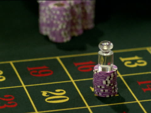 female croupier pushes thousands of dollars of winnings across roulette table to male gambler - 可能性点の映像素材/bロール