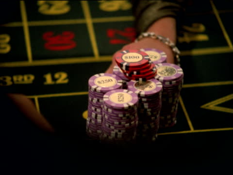 female croupier pushes thousands of dollars of winnings across roulette table towards male gambler - 可能性点の映像素材/bロール