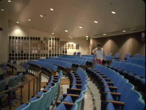 WS, Female custodian vacuums university lecture hall, Reno, Nevada, USA