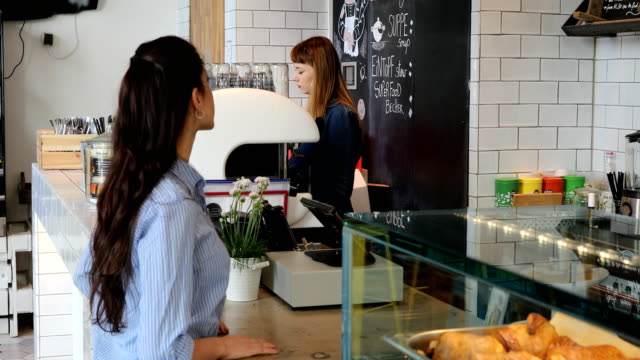 Female Customer And Barista At Cafe Counter