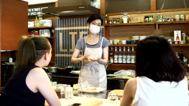 a female customer and the manager chatting in a cafe that has reopened for business - only japanese stock videos & royalty-free footage