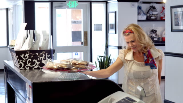 ms female customer approaches counter at candy shop and is handed a box of toffee / rancho mirage, california, usa - toffee stock videos & royalty-free footage