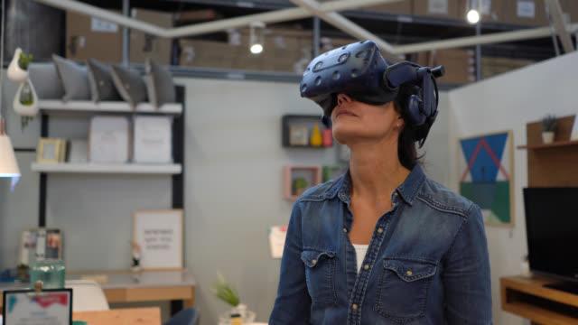 vidéos et rushes de client féminin à un magasin de meubles faisant une visite de réalité virtuelle avec un casque - réalité virtuelle