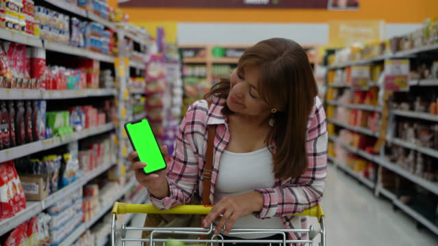 female customer leaning on cart while showing screen on smartphone facing camera smiling - copy space - market retail space stock videos & royalty-free footage